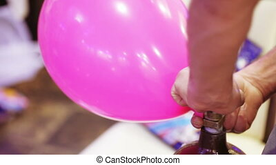 Inflating air balls - Gas cylinder inflates balloons and...