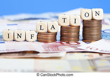 """Background of Euro banknotes on the ground, heaps of cent coins on top building a growth chart. Letter dices forming the word """"Inflation"""". Short Depth of field with front and back part blurred out of focus."""