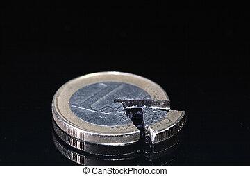 Euro coin and coin's part lying on dark background
