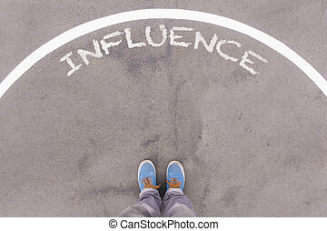 Influence text on asphalt ground, feet and shoes on floor, personal perspective footsie concept