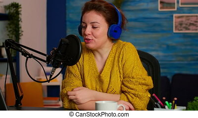 Famous influencer with headphones checking sound before live vlogging for social media, in home podcast studio. On-air online production internet broadcast show host streaming live content