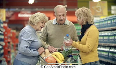 Close up of three people looking at the mineral water contents written on the bottle