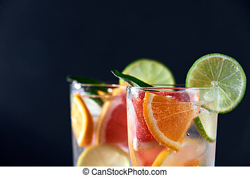 Infused water with grapefruit, orange, lemon, lime and ice on dark background