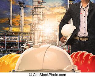 ingénierie, homme, à, blanc, casque sûreté, debout, devant, raffinerie pétrole, structure bâtiment, dans, lourd, industrie pétrochimique