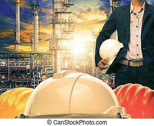 ingeniería, hombre, y, casco de seguridad, contra, refinería de petróleo, industrias, planta