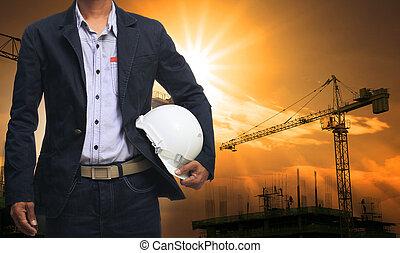 ingeniero, hombre estar de pie, con, blanco, casco de seguridad, contra, hermoso
