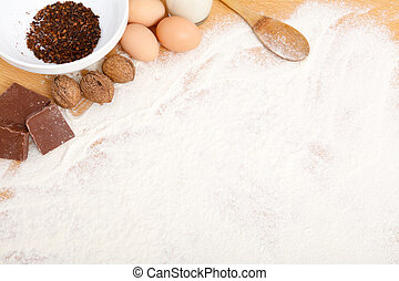 Food ingredients in flour on wooden table - copy space.