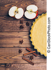 Ingredients for apple tart, apples and cinnamon on rustic wooden background.