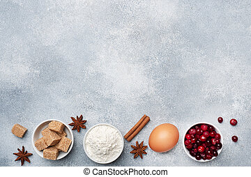 Ingredients for baking cookies, cupcakes and cake. Raw foods eggs flour sugar cranberries on a grey background with copy space.