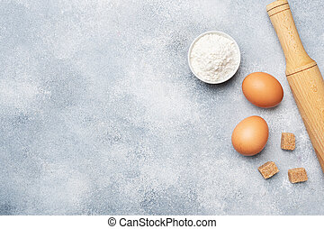 Ingredients for baking cookies, cupcakes and cake. Raw foods eggs flour sugar on a grey background with copy space.