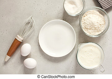 Ingredients for baking with flour and a cooking whisk with an empty white plate. The concept of food