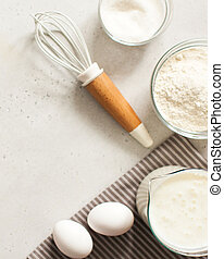 Ingredients for baking with flour and a culinary whisk with space for text, recipe. The concept of food minimalism.