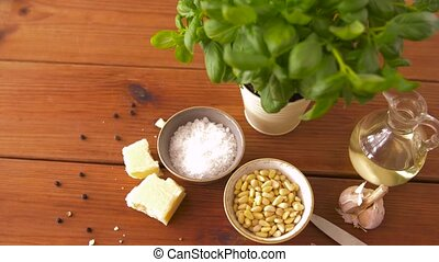 ingredients for basil pesto sauce on wooden table - food and...