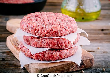 Ingredients for burgers: raw minced beef cutlets on wooden ...