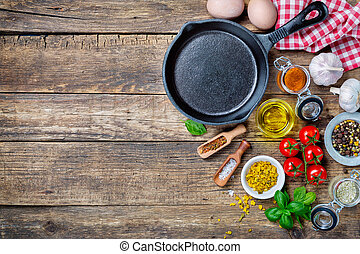 Ingredients for cooking and cast iron skillet on an old ...