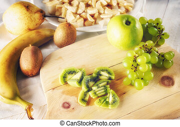 Ingredients for fruit salad. Cutting kiwi