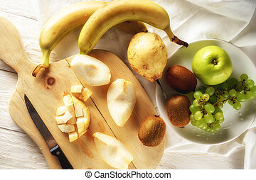 Ingredients for fruit salad. Cutting pears