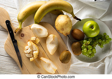 Ingredients for fruit salad. Cutting pears on a cutting board