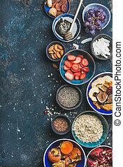 Ingredients for healthy breakfast in bowls over dark blue background, top view, copy space. Fresh and dried fruit, chia seeds, oatmeal, nuts, honey. Clean eating, vegan, detox, dieting concept