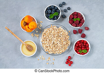 Ingredients for healthy breakfast. Oatmeal, honey with bowls of fresh summer fruits and berries: Apricot, Blueberry, Raspberry, Red Currant