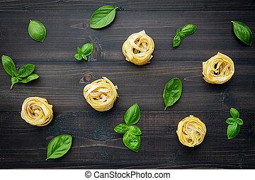 Ingredients for homemade pasta on dark wooden background.