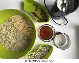 Ingredients for making homemade halva. Roasted peanuts and seeds in containers. Nearby is a coffee grinder, honey and chopped ingredients.