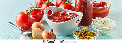 Ingredients for making speciality homemade ketchup or tomato sauce with onion, spices, tomato puree and salt in a panorama banner over light green wood