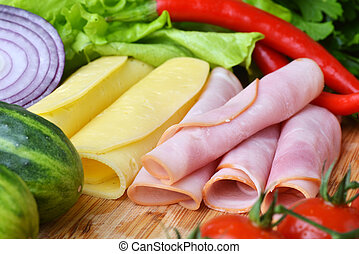 big group of meat, cheese and vegetables on a wooden table