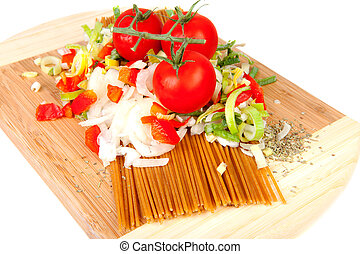 Ingredients for spaghetti on wooden cutting board