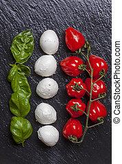 ingredients of insalada caprese on black slate