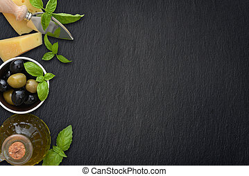 Ingredients of italian cuisine - basil, parmesan, olives and olive oil - on dark background