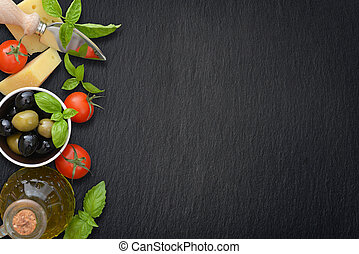 Ingredients of italian cuisine - cherry tomato, basil, parmesan, olives and olive oil - on dark background