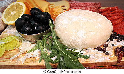 Ingredients of pizza - Pizza dough, olives, garlic, rolling...