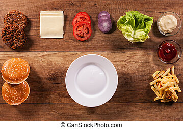 Ingredients to build the perfect hamburger - top view of wooden table