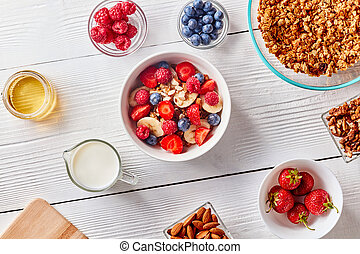 Ingredirnts for preparing healthy organic breakfast - granola, berries honey, milk, banana in white bowl on white table. Flat lay.
