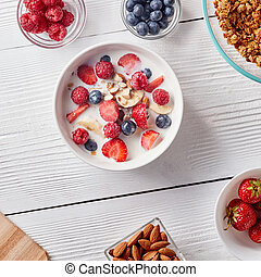 Ingredirnts for preparing healthy organic breakfast - granola, strawberries, honey, banana in white bowl with milk on white table. Flat lay.