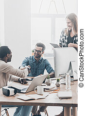 inizio, di, uno, nuovo, partnership., gruppo, di, giovane, persone affari, lavorare insieme, in, ufficio, mentre, due uomini, stringere mano, e, sorridente