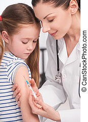 Injection. Confident female doctor doing injection to a little girl