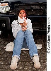 Injured after a car accident - Injured woman sitting next to...