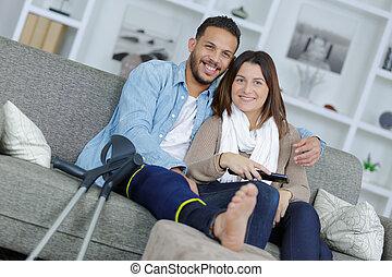 injured boyfriend and girlfriend watching tv at home