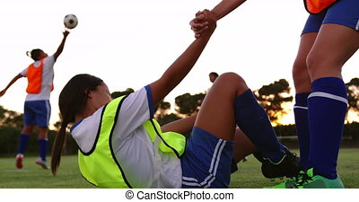 Injured female soccer player lying on the ground and getting...