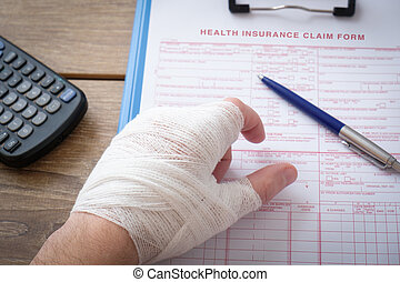Injured hand filling a insurance claim form