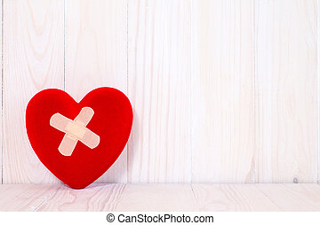 Injured heart on the white wooden background