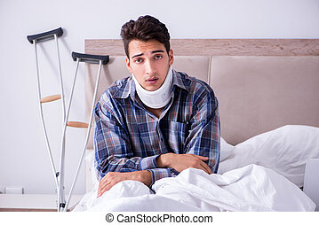 Injured man in bed at home with crutches