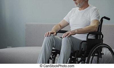Injured man in wheelchair at rehabilitation center, hopes to walk again, closeup
