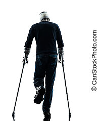 injured man walking  rear view with crutches silhouette