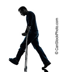 injured man walking sad with crutches silhouette
