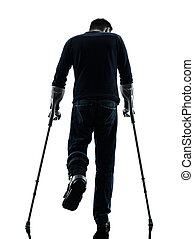injured man walking with crutches silhouette rear view - one...