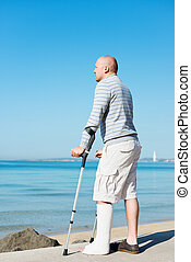 Injured Man with Crutches at sea side