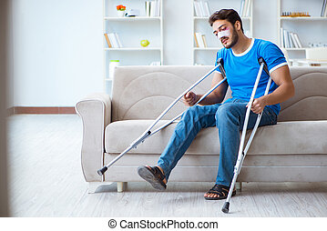 Injured man with crutches recovering at home